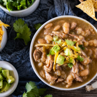 Top down view of a bowl of pork chili topped with avocado and cilantro with bowls of shredded cheese, cilantro, green onions, and tortilla chips off to the side.