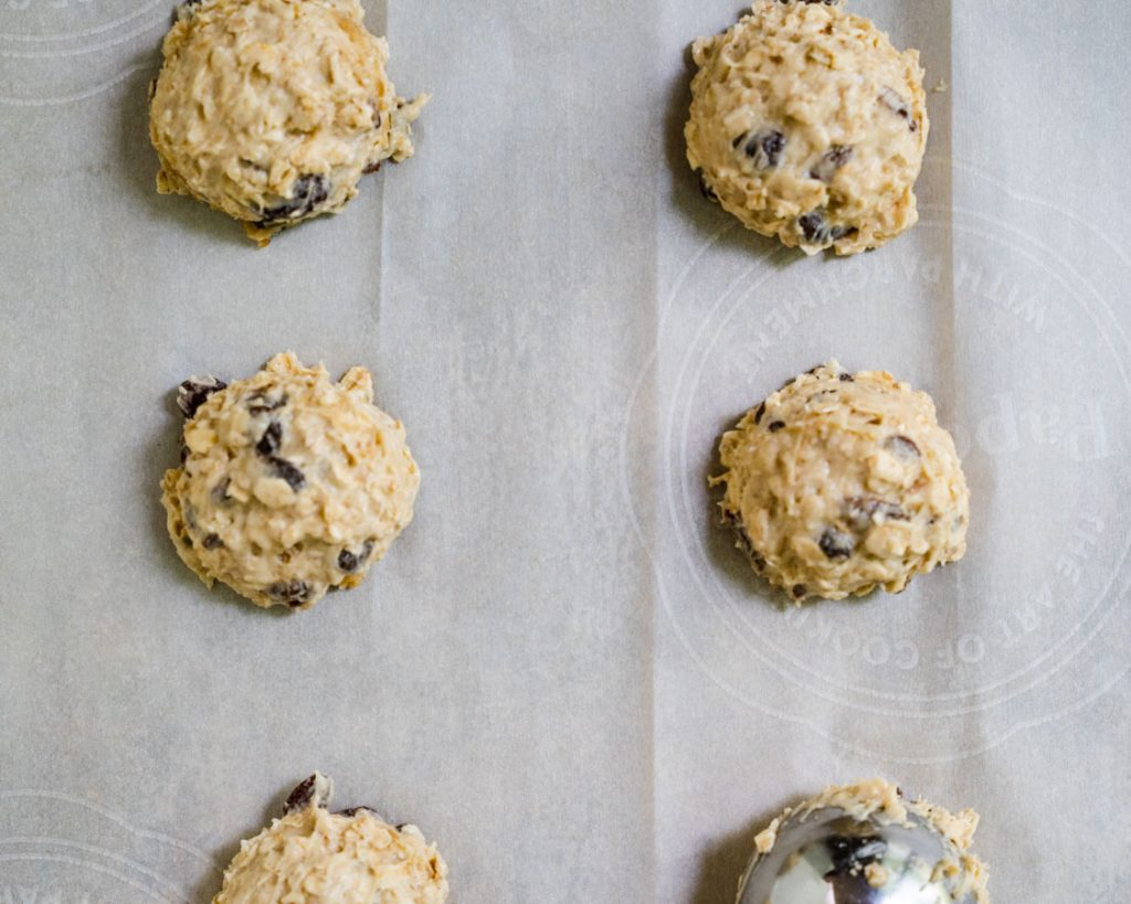 Cookie batter scooped onto parchment paper lined cookie sheet.